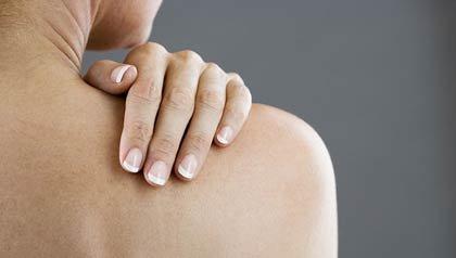 Una mujer con su mano en el hombro - Causas del dolor de hombro - Bursitis, hombro congelado