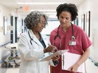 Doctors discuss patient chart, Avoid hospitals in July (Blend Images/Alamy)