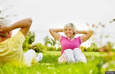 Mature couple exercising together outdoors (Getty Images)