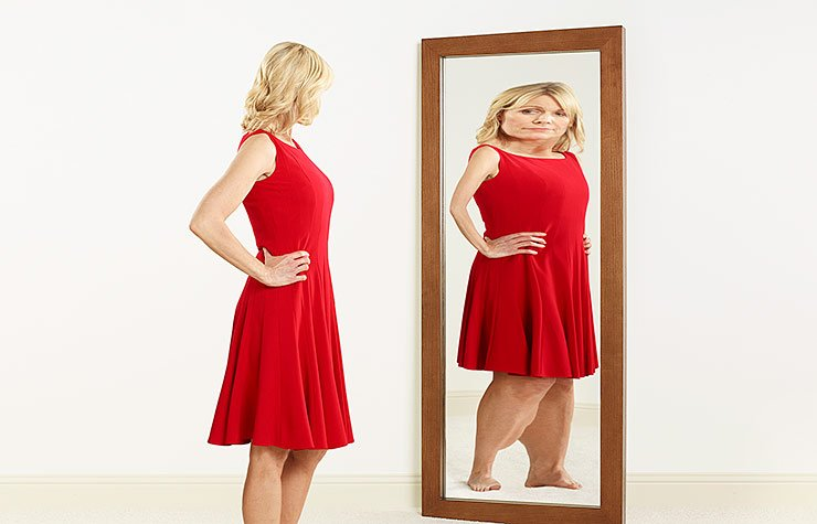 A woman with an eating disorder looks at her warped reflection in a mirror.