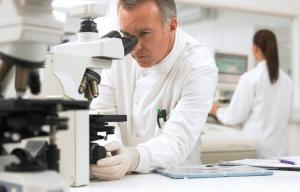 Científico que mira a través de un microscopio - Reexaminar la definición de cáncer - Que es el cáncer