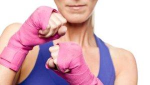 Mujer con unos guantes rosados - Cómo evitar o reducir el riesgo de padecer cáncer de mama
