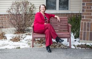 Mujer vestida de rojo sentada en un banco al aire libre - Watertown, Wisconsin una ciudad amigable para la demencia