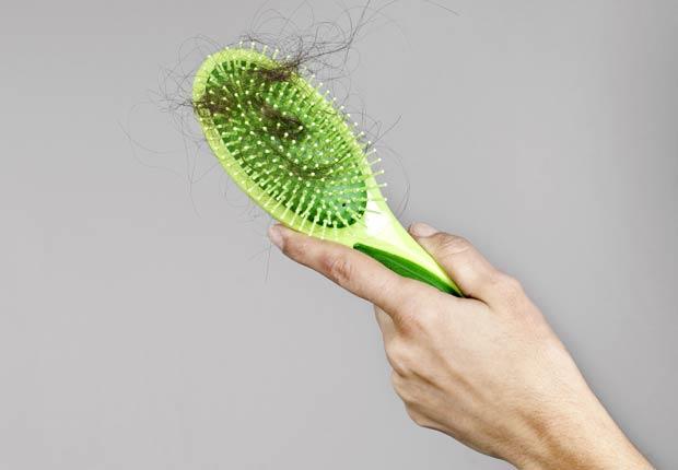 Mujer sosteniendo un cepillo de pelo, 10 Razones por las cuales usted puede estar perdiendo cabello
