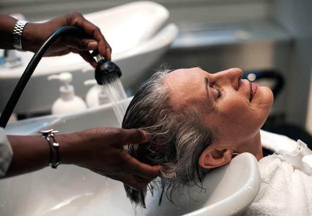 Mujer lavándose el cabello en el salón de belleza, 10 Razones por las cuales usted puede estar perdiendo cabello