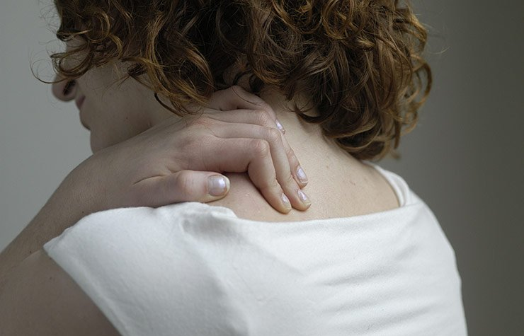 Woman rubbing her shoulder Things to know about Fibromyalgia.