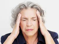 Mujer con sus manos puestas en sus cienes - Gravedad de un dolor de cabeza