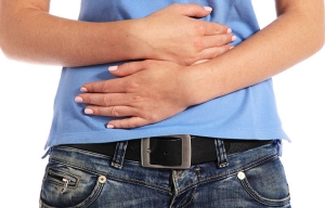 Mujer con las manos en el estómago, en señal de dolor - Problemas estomacales