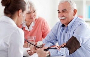Un médico toma la presión arterial de un hombre mayor - Disminuyen los casos de cáncer de colon