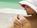 best sunscreen woman beach applying hat SPF