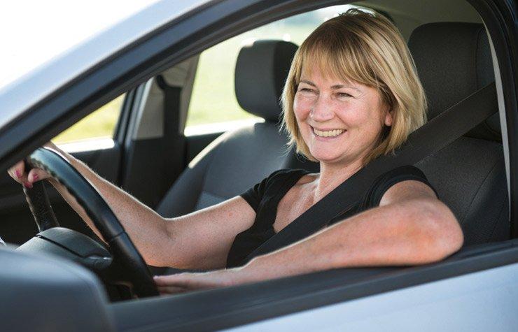Mature woman driving car, sunburn from driving