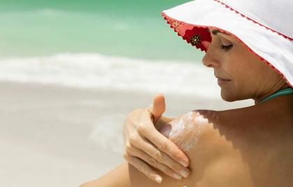 best sunscreen woman beach applying hat SPF