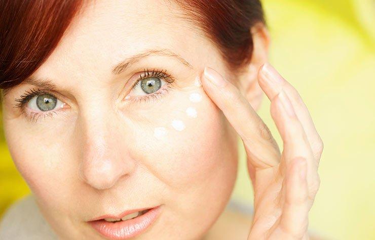 Mujer aplicándose maquillaje - 7 Hábitos que causan arrugas