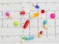 Imagen de un cardiograma con unas pastillas - Efectos secundarios de los medicamentos para la controlar la presión arterial