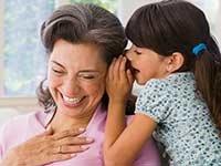 Niña hablándole al oido a una mujer - Centro de recursos para la pérdida de audición