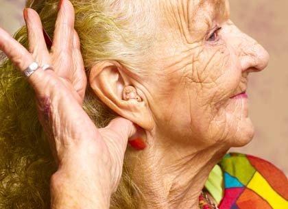 Mujer mayor con un audífono - Ayudas para la audición