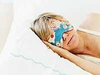 Mujer durmiendo con una mascarilla puesta - El beneficio de dormir para la salud de tu cerebro