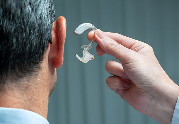 Doctor inserting hearing aid in man's ear, How to Get the Right Hearing Aid: 10 Tips