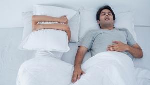 Pareja en la cama, mujer tapándose la cara con una almohada, hombre durmiendo - La apnea del sueño en las personas mayores