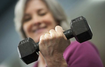Mujer levantando una mancuerna - Cómo fortalecer tus huesos a cualquier edad