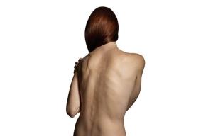 Mujer de espaldas, desnuda y agarrándose un hombro - Formas de manejar el dolor