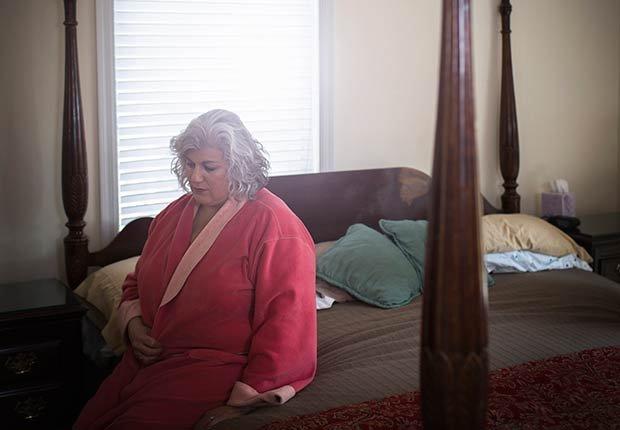 Mujer obesa sentada en una cama - Mitos y verdades sobre las enfermedades de la tiroides