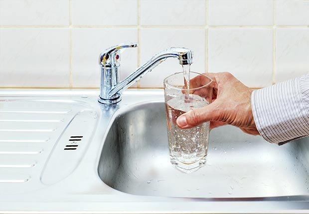 Llenando un vaso de agua en el fregadero - Cómo cuidar y mantener tus riñones saludables