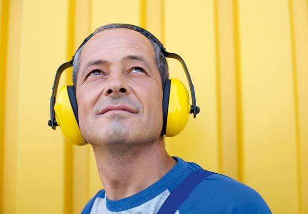 Hombre con audífonos - Pérdida auditiva por ruido