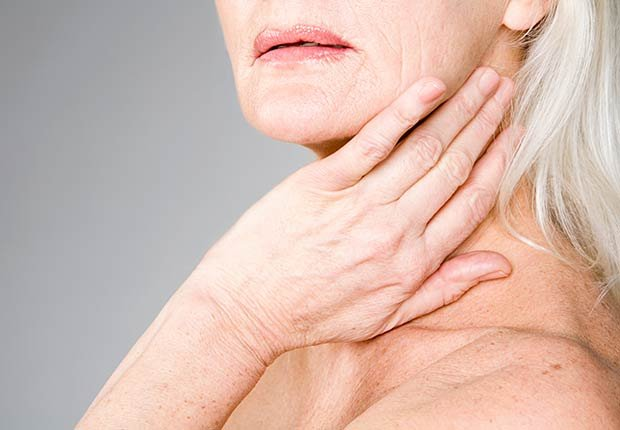 Mujer palpandose el cuello - Mitos y verdades sobre las enfermedades de la tiroides
