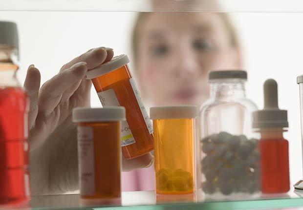 Mujer tomando un frasco de medicamentos - Mitos y verdades sobre las enfermedades de la tiroides
