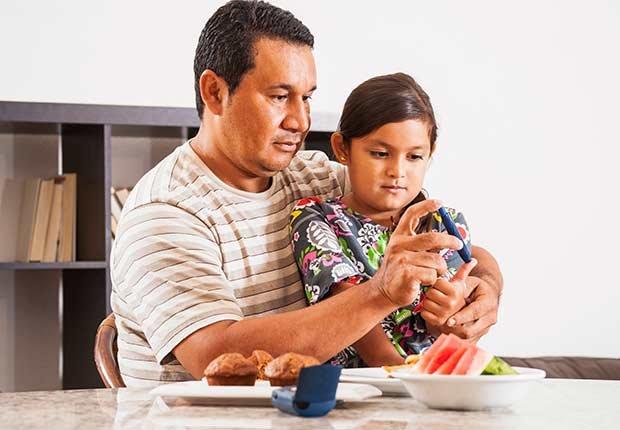 Padre tomando muestra de sangre a su hija - Diabetes tipo 1 en niños