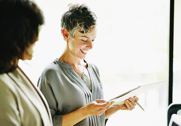 Dos mujeres revisando un documento - Pérdida de audición y trabajo
