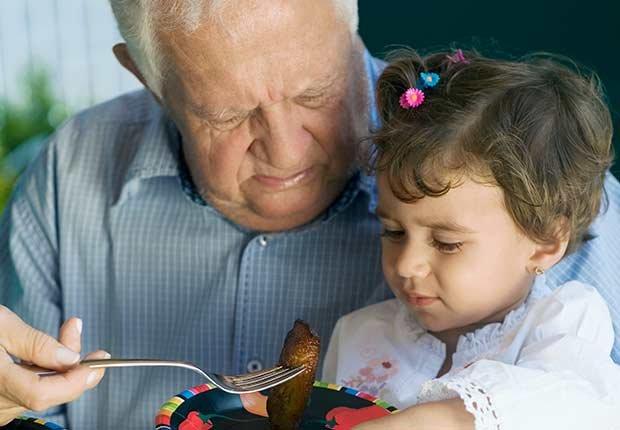 Abuelo dándole de comer a su nieta - Diabetes tipo 1 en niños