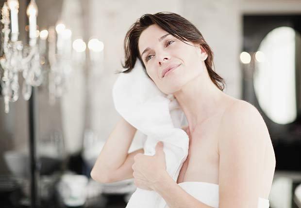 Mujer secándose luego de ducharse - Cómo proteger tus oídos