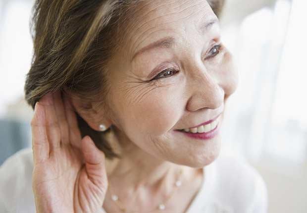 Mujer haciendo el esfuerzo de escuchar - Pérdida de audición y trabajo
