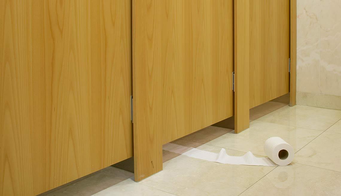 Baño público y papel higiénico rodando por el piso