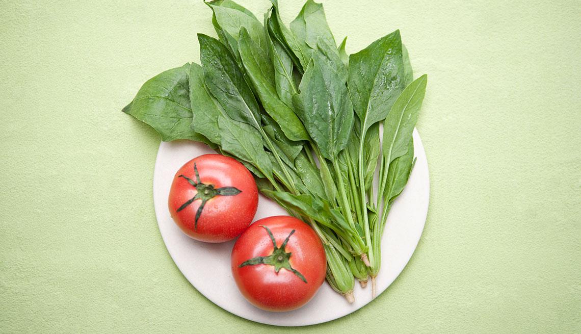 Hojas de espinaca y tomates en un plato