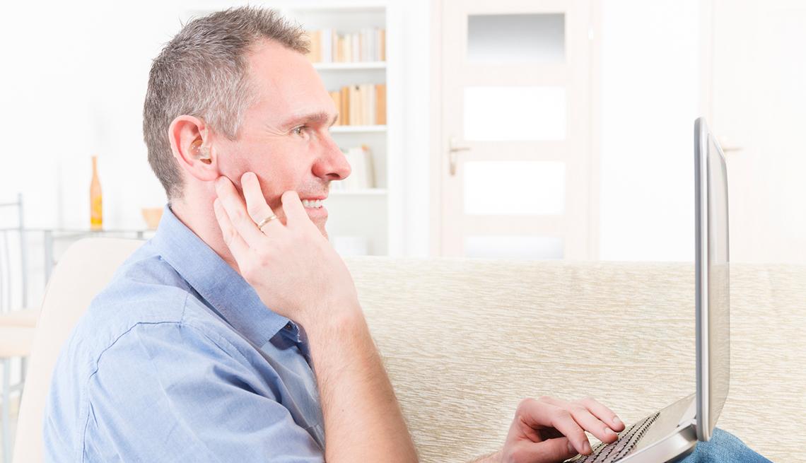 Hombre con problemas auditivos utilizando una computadora