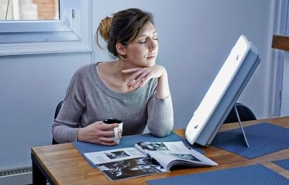 Mujer tomando café mientras está en una sesión de fototerapia
