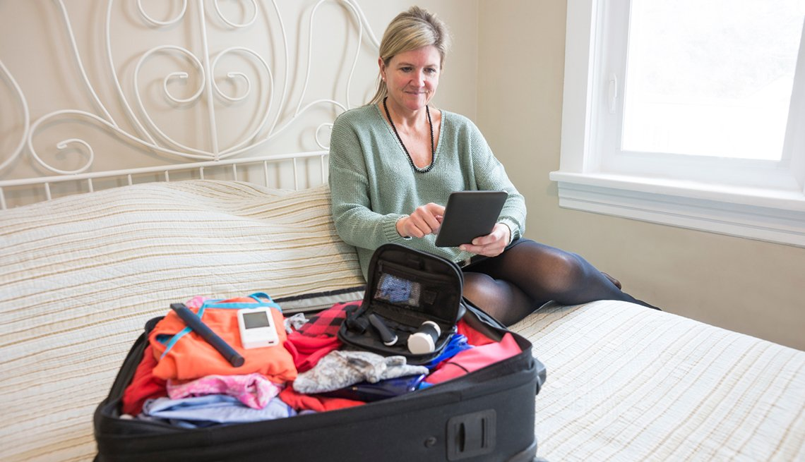 Woman packing her bag and hearing aid device