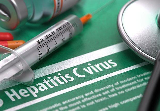Jeringuilla y estetoscopio sobre documento de la Hepatitis C