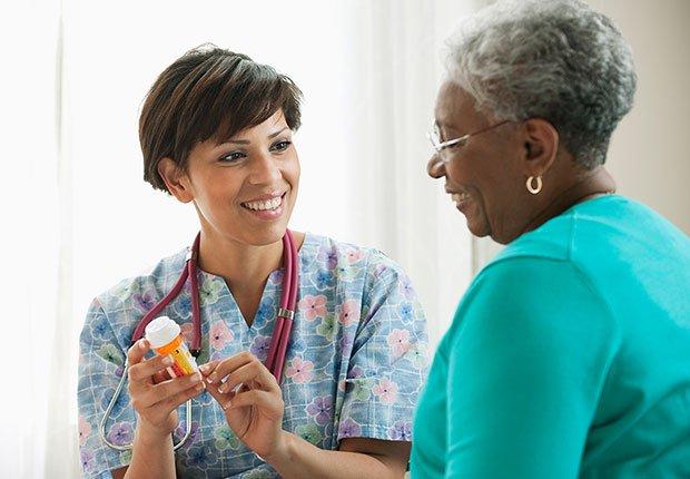 Enfermera con un pote de medicamentos conversando con un paciente