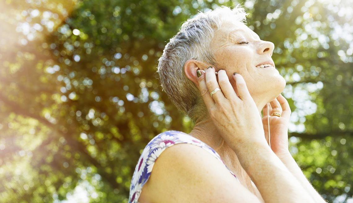 Mujer escuchando música con audífonos - Pérdida auditiva