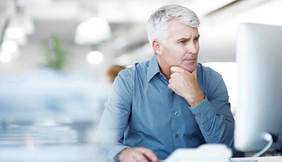 Man looking concerned working on his computer