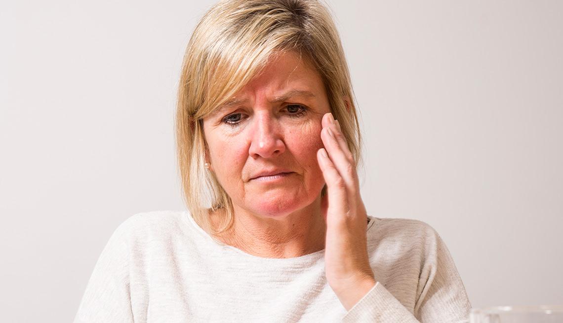 Mujer con su mano en el rostro en gesto de dolor - Medicamentos y la pérdida auditiva