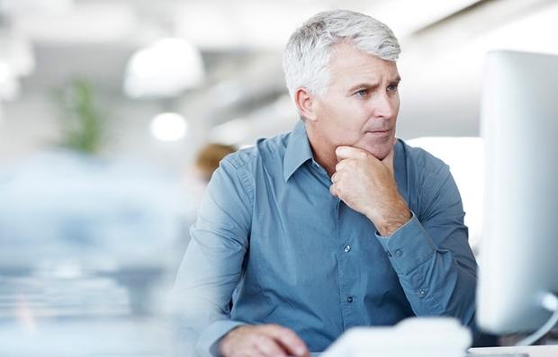 Hombre mayor sentado frente a una pantalla de computador - Cómo enfrentar la pérdida auditiva en el lugar de trabajo