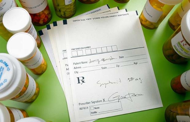 Botellas de medicamentos rodeando recetas médicas