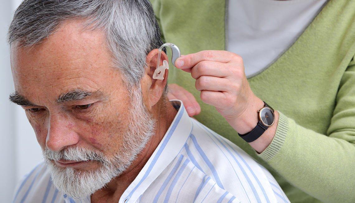 Médico colocando un audífono a un paciente - Pérdida de audición