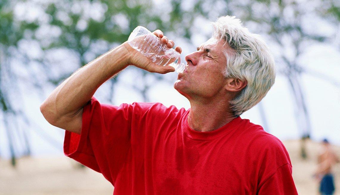 Hombre tomando agua embotellada