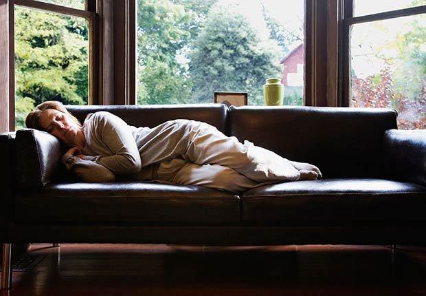 Adulto tomando una siesta en un sofá